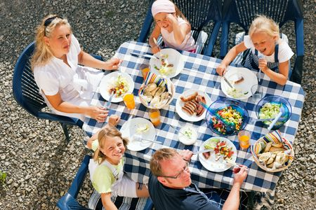 garden party: Family having dinner in their garden - barbecue stuff and salad Stock Photo