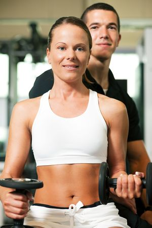Woman with her personal fitness trainer in the gym exercising with dumbbells Stock Photo - 6171445