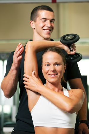 Woman with her personal fitness trainer in the gym exercising with dumbbells Stock Photo - 6171465