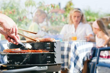 Familie een barbecue hebben in de tuin - de focus op het koken op de voorgrond