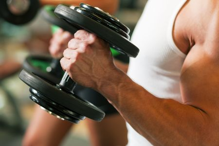 Strong man exercising with dumbbells in a gym, in the background a woman also lifting weights; focus on hands photo