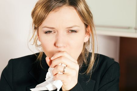 coughing: Woman having a cold, coughing, holding a handkerchief in front of her face Stock Photo