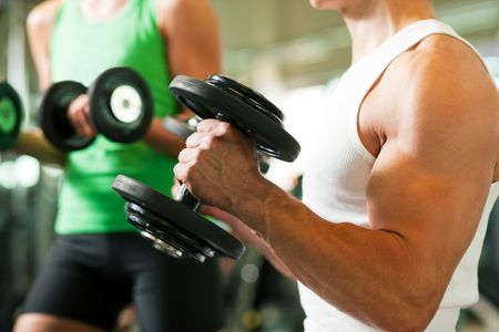 Strong man exercising with dumbbells in a gym, in the background a woman also lifting weights; focus on hands Stock Photo - 6171472