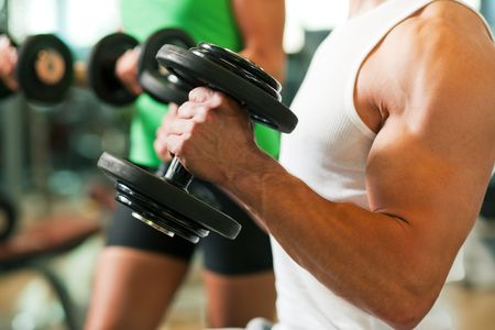 lifting: Strong man exercising with dumbbells in a gym, in the background a woman also lifting weights; focus on hands