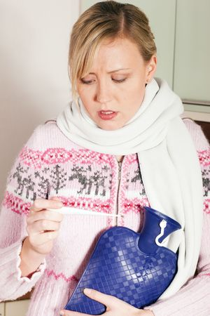 Woman with flu taking her temperature, looking at the thermometer having a hot water bag in her hand photo