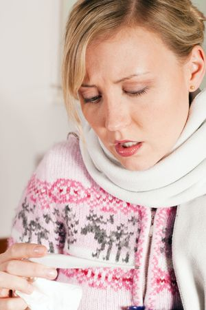 Woman with flu taking her temperature, looking at the thermometer  photo