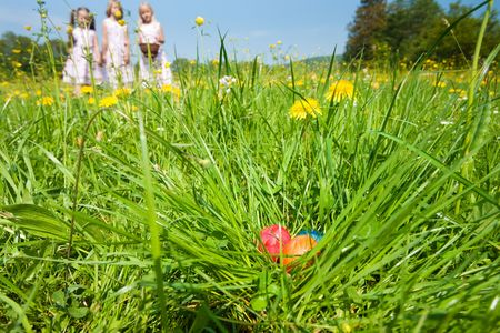 Easter eggs in the grass - in a nest - waiting to be found by children who are already on the hunt photo