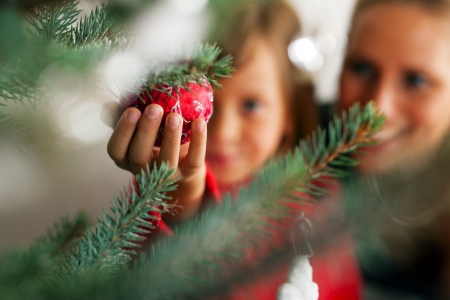 Young girl helping her mother decorating the Christmas tree, holding some Christmas baubles in her hand (Focus on bauble) photo