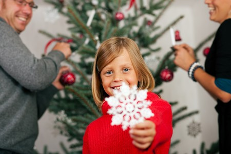Young girl helping her family decorating the Christmas tree, holding a Christmas Snowflake in her hand photo