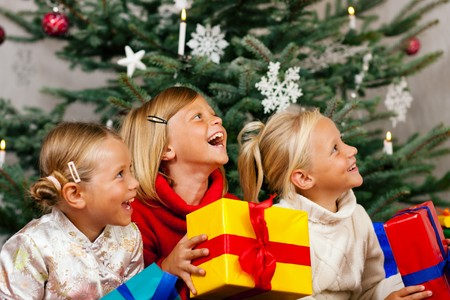 father christmas: Family Christmas - three children having received gifts showing them around
