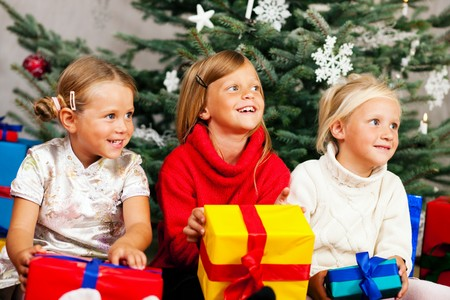 received: Family Christmas - three children having received gifts showing them around