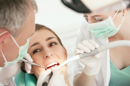 Female patient with dentist and assistant in the course of a dental treatment, wearing masks and gloves  Stock Photo - 8037031