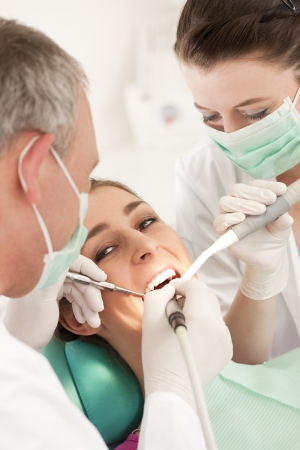 Female patient with dentist and assistant in the course of a dental treatment, wearing masks and gloves  photo