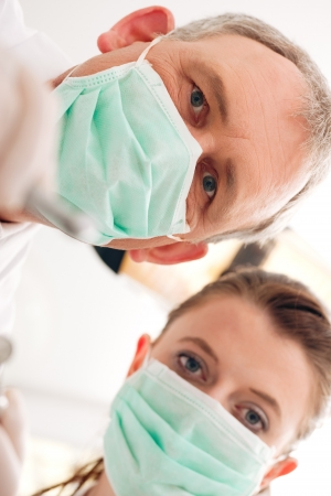 Dental treatment with dentist and dental assistant bowing over the patient as seen from patients perspective. They have drills and angled mirrors, focus on eyes of dentist  photo
