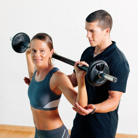 personal trainer: Woman with her personal fitness trainer in the gym exercising power gymnastics with a barbell