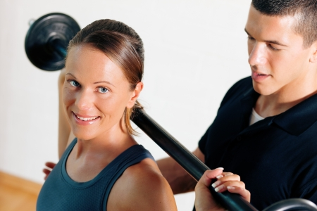 Woman with her personal fitness trainer in the gym exercising power gymnastics with a barbell photo