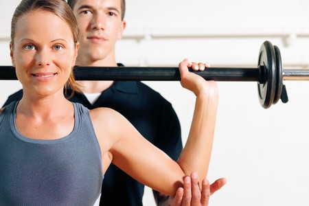 trainer: Woman with her personal fitness trainer in the gym exercising power gymnastics with a barbell