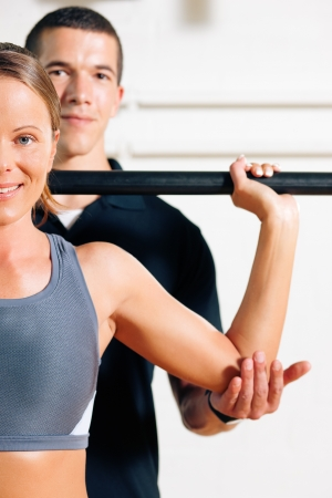 Woman with her personal fitness trainer in the gym exercising power gymnastics with a barbell Stock Photo - 8037037