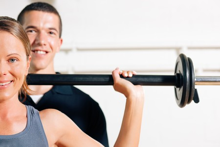 Woman with her personal fitness trainer in the gym exercising power gymnastics with a barbell Stock Photo - 8037022