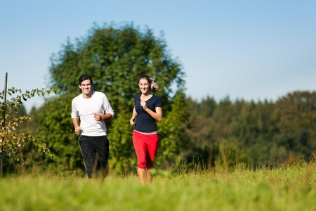 Young fitness couple doing sport outdoors, jogging on a green summer meadow in the grass under a clear blue sky photo