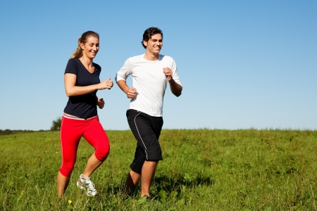 exercising: Young fitness couple doing sport outdoors, jogging on a green summer meadow in the grass under a clear blue sky Stock Photo