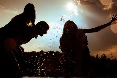 unbelievable: Personas (dos parejas), sinti�ndose muy libre en la permanente puesta del sol en el agua salpicando agua unos a los otros una cantidad incre�ble de diversi�n. Siluetas.  Foto de archivo