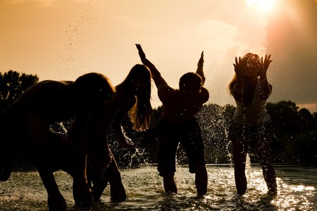 People (two couples) feeling very free in the sunset standing in the water splashing water at each other having an unbelievable amount of fun. Silhouettes. Stock Photo - 8037042