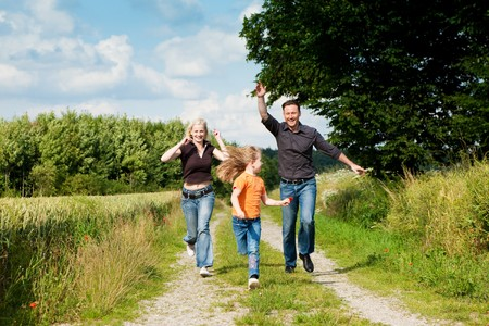 Happy family (mother, father and kid) having a walk in the nature playing tag photo