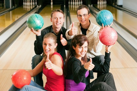 focus group: Group of four friends in a bowling alley having fun, holding their bowling balls and showing thumbs up (focus on guys in second row)