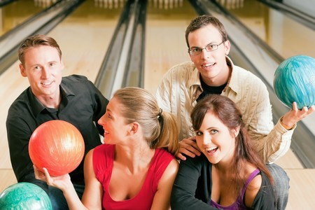 Group of four friends in a bowling alley having fun, holding their bowling balls and flirting with each other (focus on girls in front row) photo