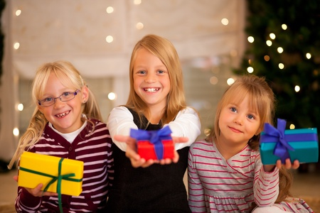 three presents: Three Girls in front of a Christmas tree with presents