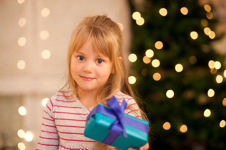 Girl in front of a Christmas tree with presents photo