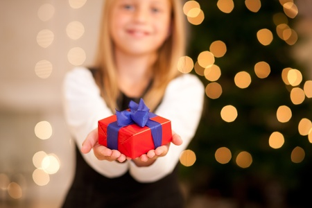 Girl in front of a Christmas tree with presents, FOCUS is only on the present photo