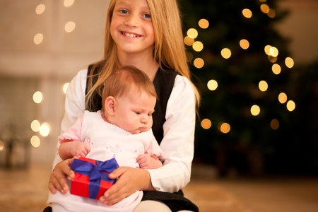 Two sisters - one is still a baby - in front of a Christmas tree with presents photo