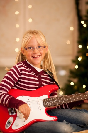 Young child with her guitar - presumably a present - in front of a Christmas tree photo