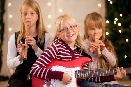 making music: Young children with guitars and flutes - presumably presents - in front of a Christmas tree making music