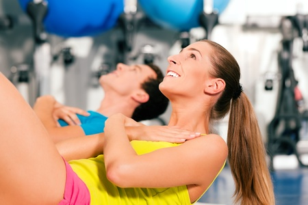 two people, man and woman, exercising doing sit-ups in the gym for better fitness photo