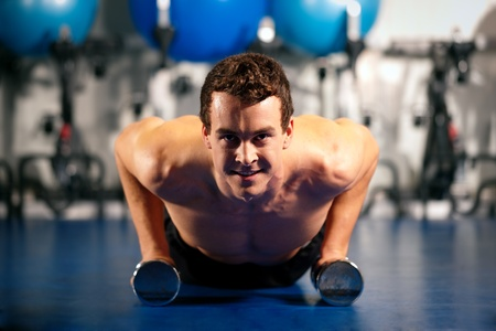 Very strong and muscular man exercising by doing pushups in a gym Stock Photo - 8295206
