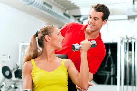 athletic activity: Young woman lifting a dumbbell in the gym assisted by her personal trainer (focus on woman)