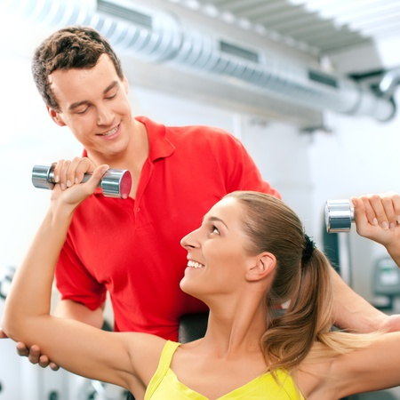 Young woman lifting a dumbbell in the gym assisted by her personal trainer (focus on woman) photo