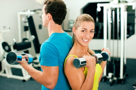 couple in the gym, rivaling each other, exercising with dumbbells Stock Photo - 8295286