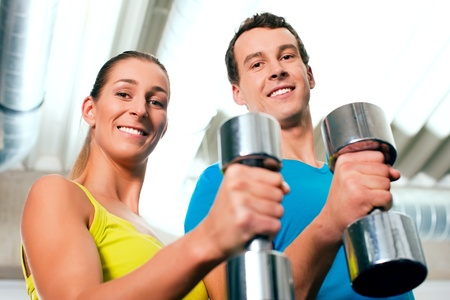 couple in the gym, rivaling each other, exercising with dumbbells Stock Photo - 8295244