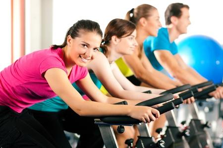 hombres haciendo ejercicio: Grupo de cuatro personas girando en el gimnasio, ejercer sus piernas haciendo entrenamiento de cardio