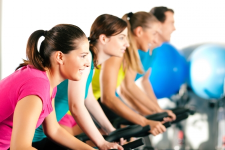 stationary bike: Group of four people spinning in the gym, exercising their legs doing cardio training Stock Photo
