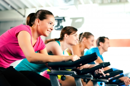 fitnes: Group of four people spinning in the gym, exercising their legs doing cardio training Stok Fotoğraf