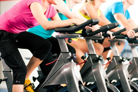 cardio fitness: Group of four people spinning in the gym, exercising their legs doing cardio training Stock Photo