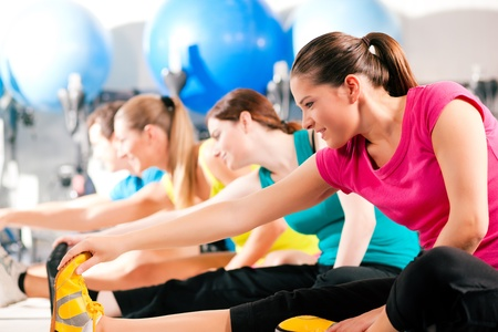 warming up: Group of four people in colorful cloths in a gym doing aerobics or warming up with gymnastics and stretching exercises