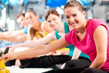 Gruppe von vier Personen in bunten Tüchern in ein Fitness-Studio Aerobic tun oder Aufwärmen mit Gymnastik und stretching-Übungen