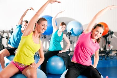 krachtige vrouw: Vier mensen - man en vrouw - in de sportschool doen gymnastiek op een oefening bal