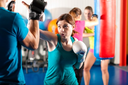boxing training: Woman Boxer hitting the sandbag, her trainer is assisting